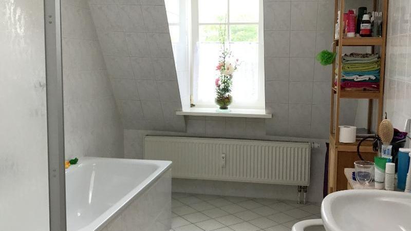 sowie ein befenstertes Badezimmer mit Badewanne und Dusche.